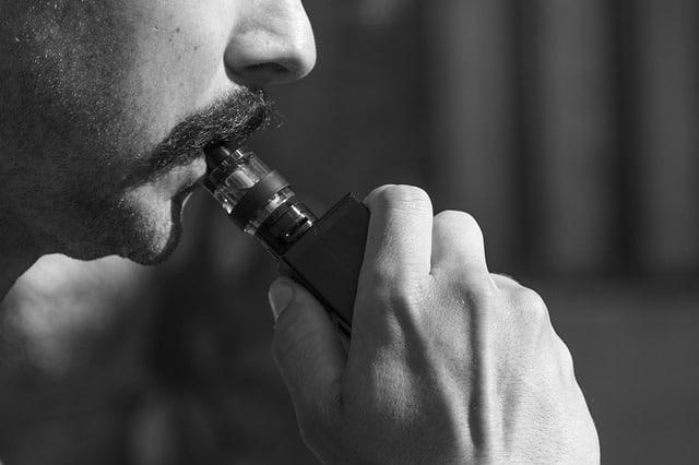 homme à moustache avec sa cigarette électronique